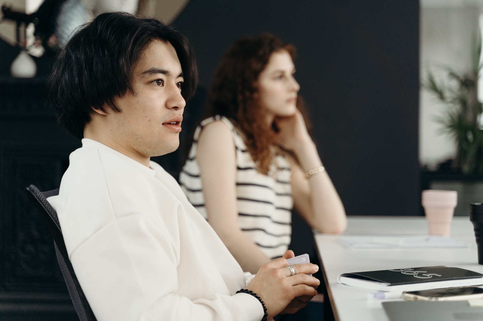 man in white sweater sitting beside a woman