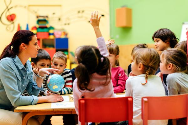 Preschool teacher and children in classroom