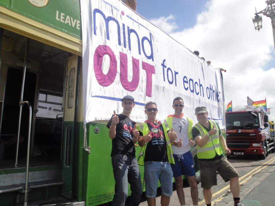 volunteers and staff beside the MindOut bus before it sets off for the parade