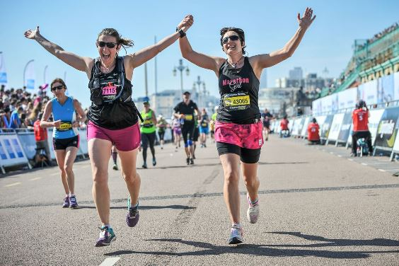 two runners cheer as they complete the marathon on brighton seafront