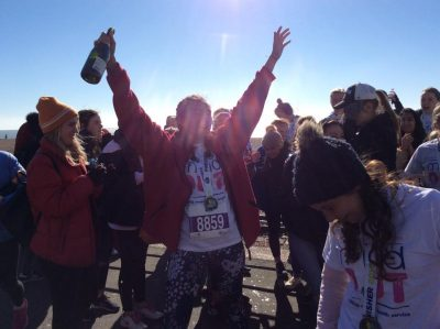 a runner cheering with a bottle of champagne