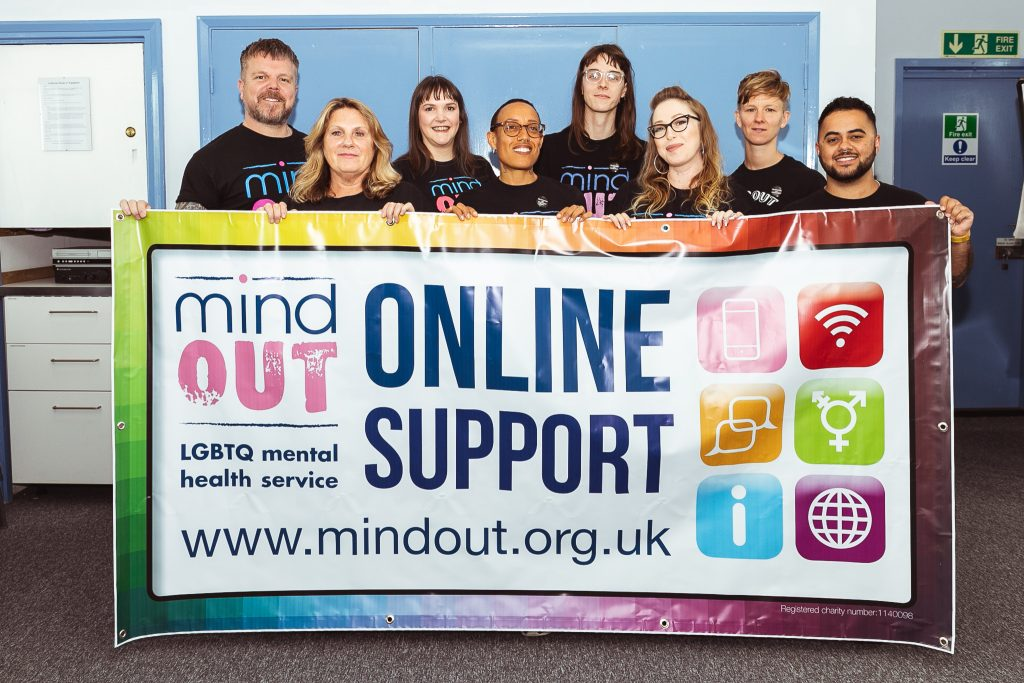 mindout staff holding a large colourful banner for the online support service