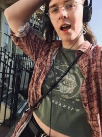 white woman walking down the street, wearing headphones, glasses, a brown shirt and a green top.
