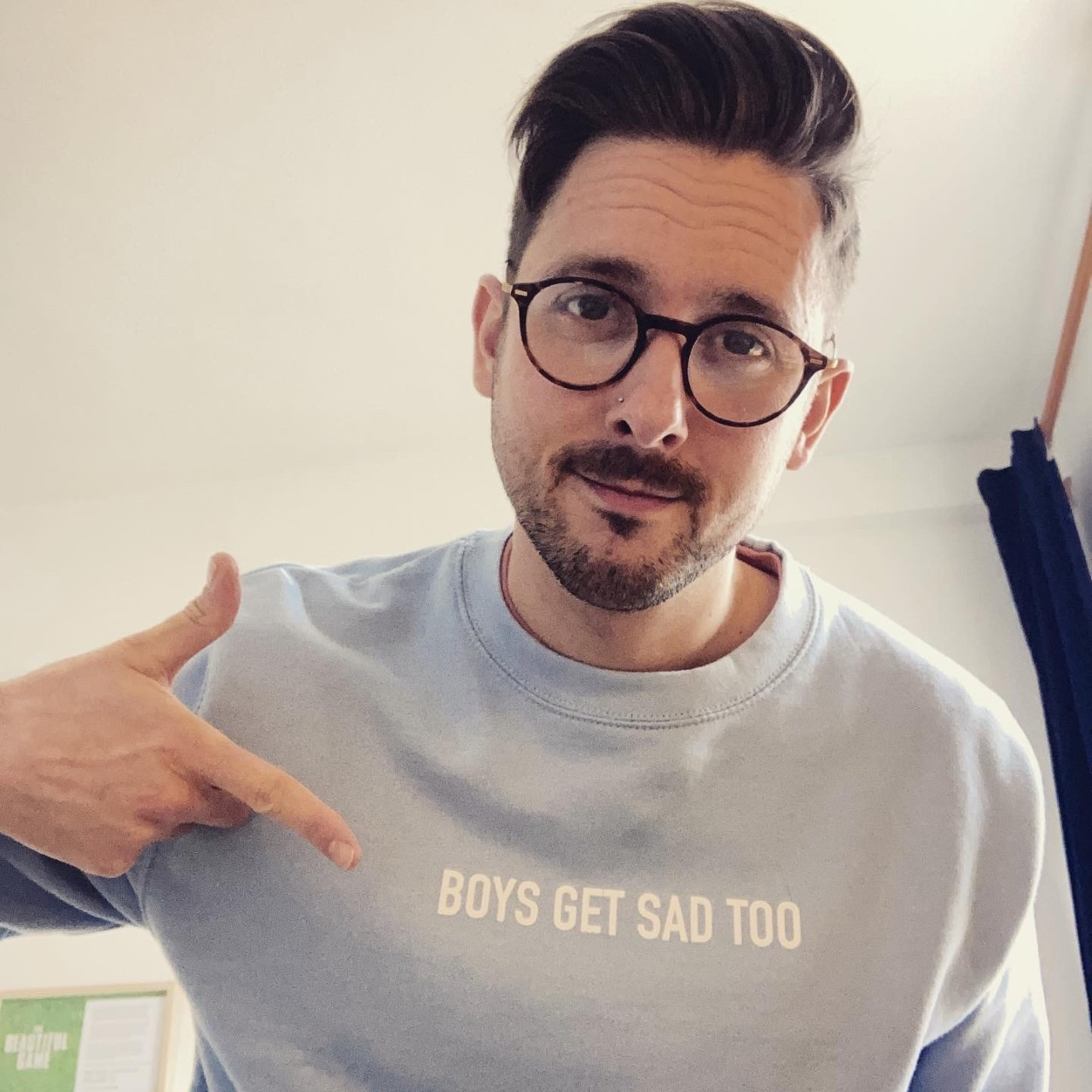 Charlie, a MindOur Volunteer, wearing a T shirt with the slogan Boys Get Sad Too