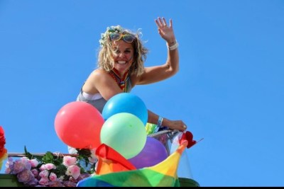 White woman, with colourful balloons, holding her arm up in the hair