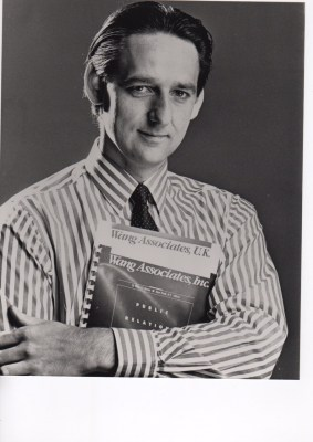 White man with dark hair, who's wearing a stripy shirt with a tie, and he's holding a book in his arms
