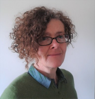 Helen wearing a green jumper with a blue colour, and glasses, turned to the side and looking at the camera