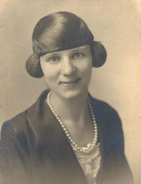 picture of a lady fro m 1930 in a suit wearing pearls