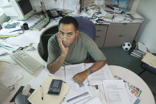 A man sitting at a desk with paperwork spread all around.