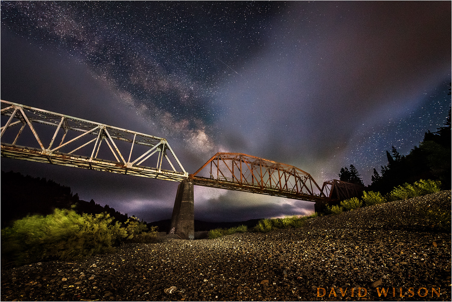 Abandoned Railroad trestle spans a riverbed beneath the Milky Way
