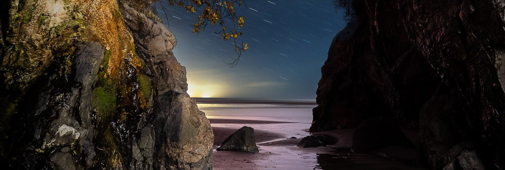 Panoramic crop of view through Moonstone Beach cave's mouth into the night.