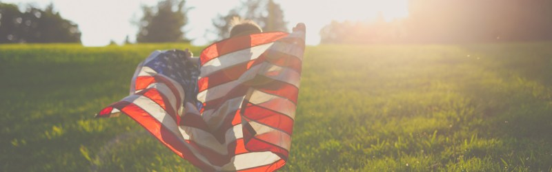 A child running with an American flag in a field towards a sunset