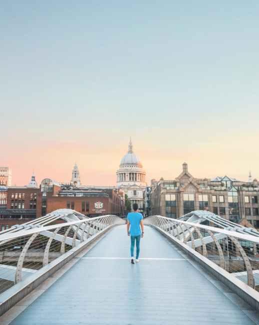 man in teal shirt walking on bridge