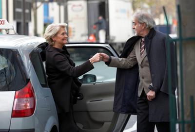 мужчина помогает женщине выйти из такси