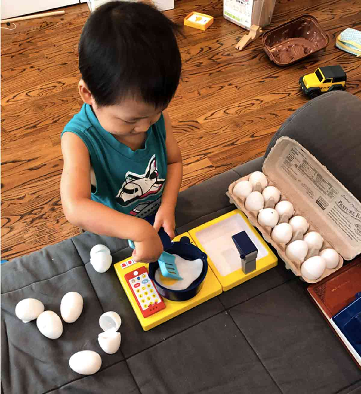 oddler playing with pretend play felt egg on toy cooking pot