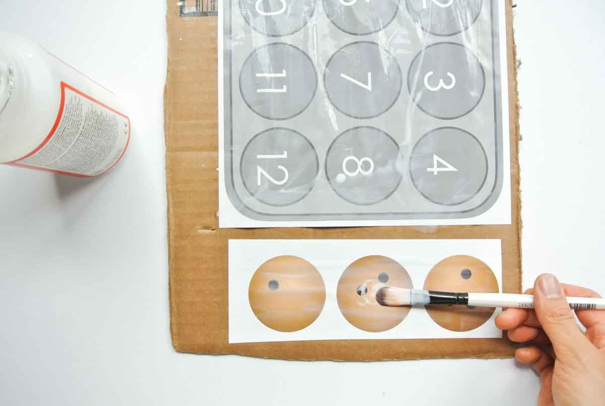 applying modpodge to cookie sheet and cookies. toddler cookie counting activity free printable