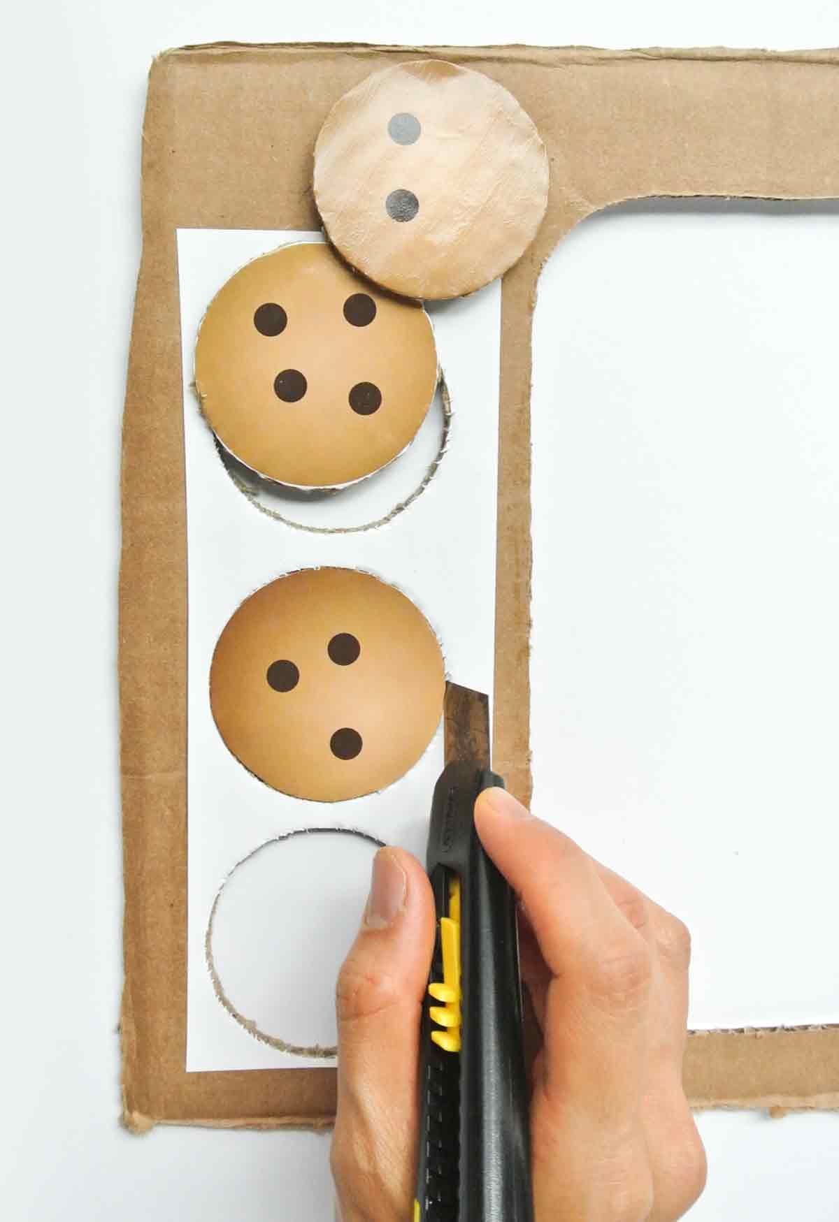 Cutting out cardboard chocolate chip cookies with x-acto knife