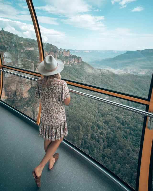 stylish woman standing on observation deck above mountains