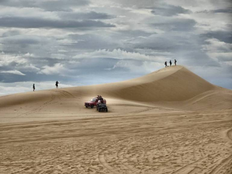 Jeeps und Menschen in den Sanddünen