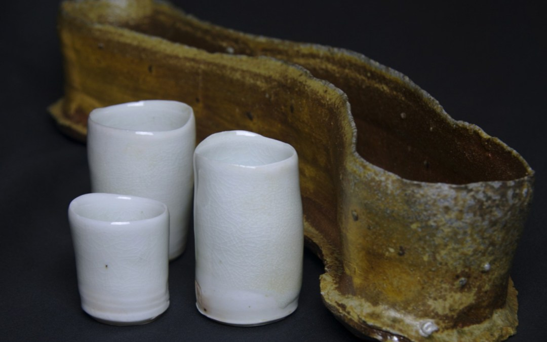 """Snake"" food fired tray peeking out behind three Chalice cups"