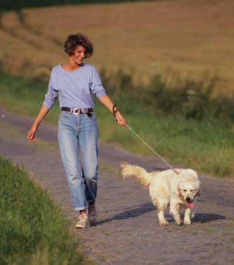 Lady walking her dog at a pet boarding facility