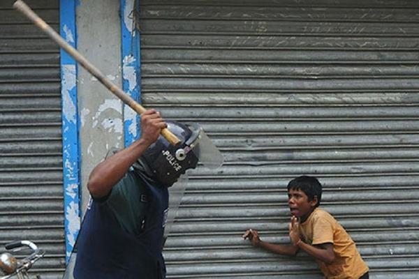 Criança sendo espancada por policial em protesto em Bangladesh, em 2010.