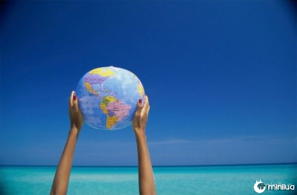Person holding up a globe at the beach