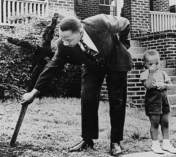 Martin Luther King y su hijo removiendo una cruz quemada que miembros del KKK dejaron frente a su casa en 1960.