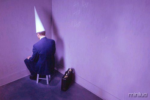 businessman-sitting-in-corner-with-dunce-hat