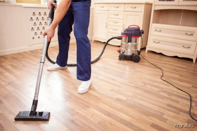 Close up of male legs standing in a room. The man is vacuuming floor in his house