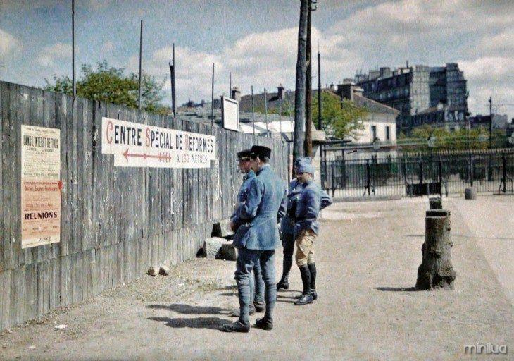 Paris soldados lendo um cartaz na parede