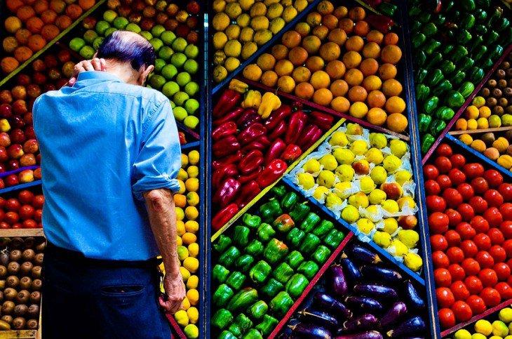 homem diante de uma prateleira cheia de frutas e legumes perfeitamente ordenado