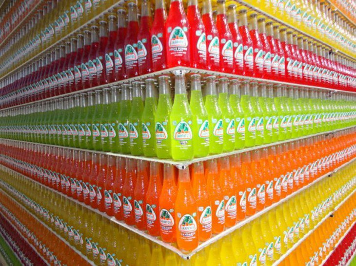 garrafas de vidro Jarritos acomodados por cores e sabores