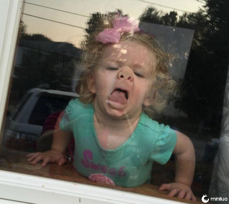 O rosto de menina colado a um vidro