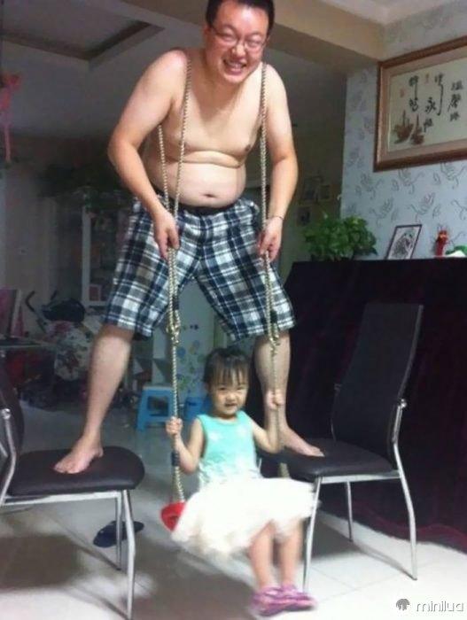 homem com bermuda xadrez balançando uma garota