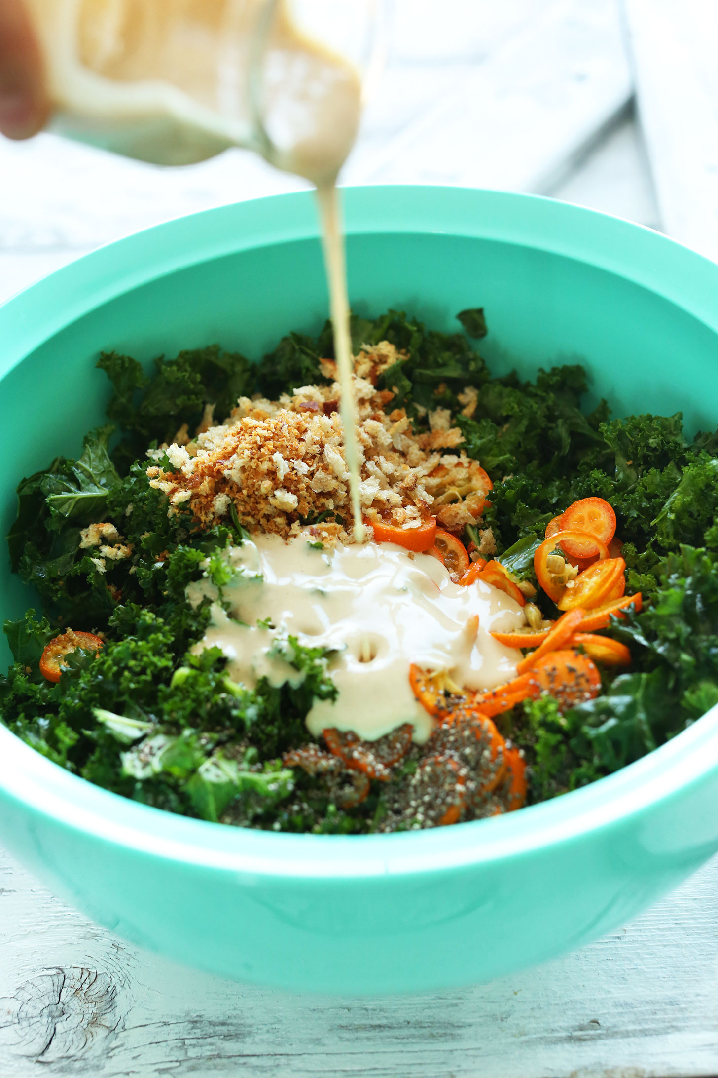 Kumquat Kale Salad   Minimalist Baker Recipes Pouring Tahini Dressing onto our delicious vegan Kale Salad with Kumquats