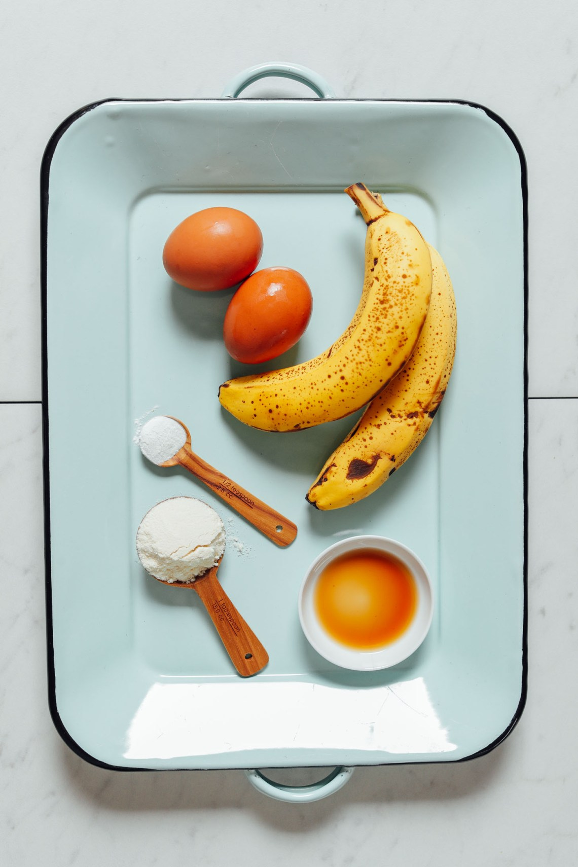 Tray with 5 simple ingredients for making Banana Egg Pancakes