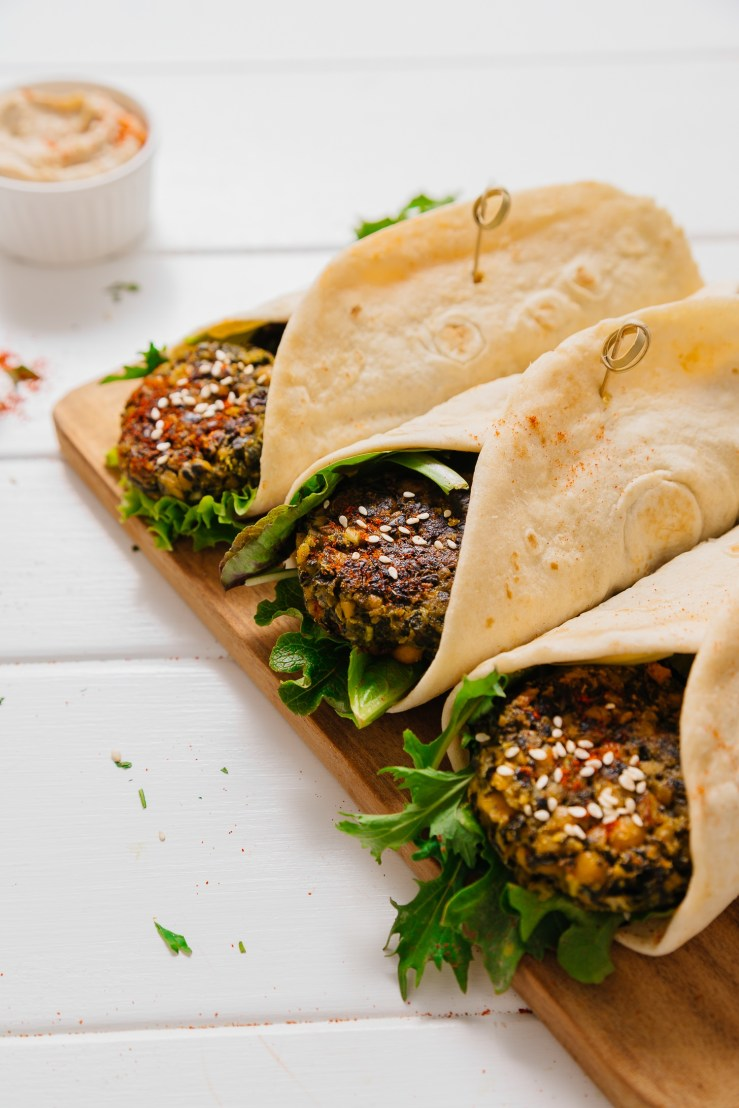 Cutting board with Kale Falafel Hummus Wraps made with pita bread and fresh greens