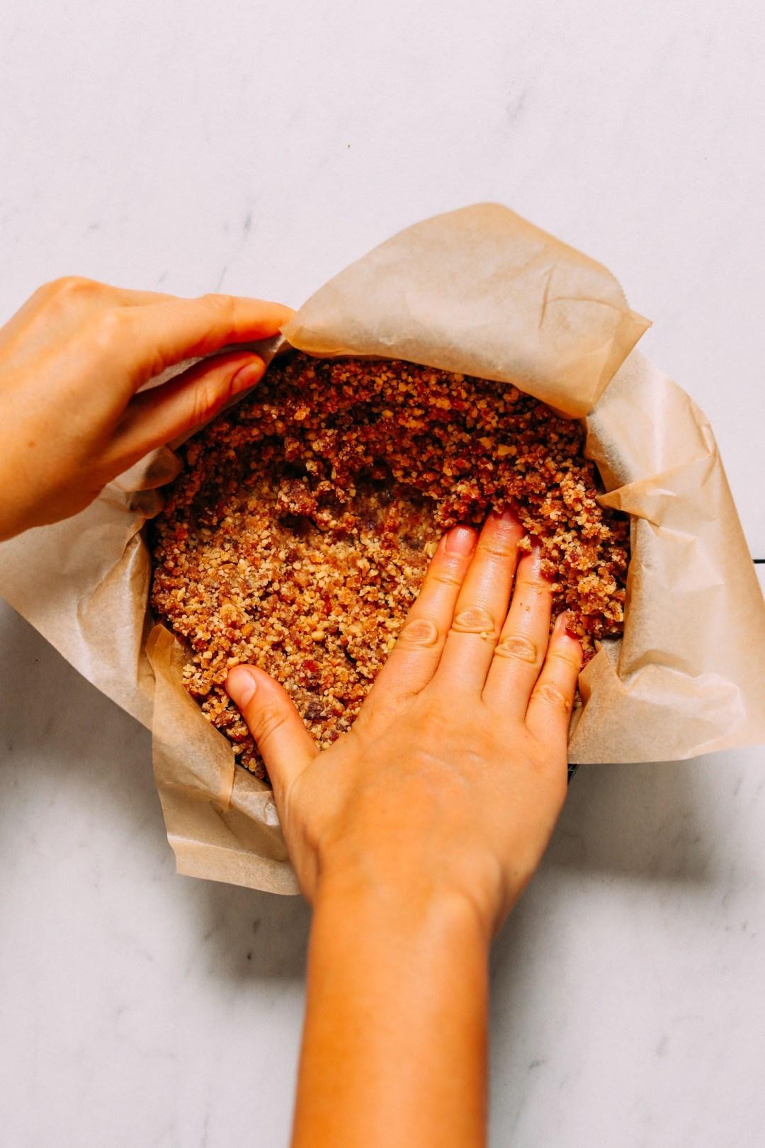 Al presionar la corteza de tarta de queso sin hornear de nuez en una sartén forrada de pergamino
