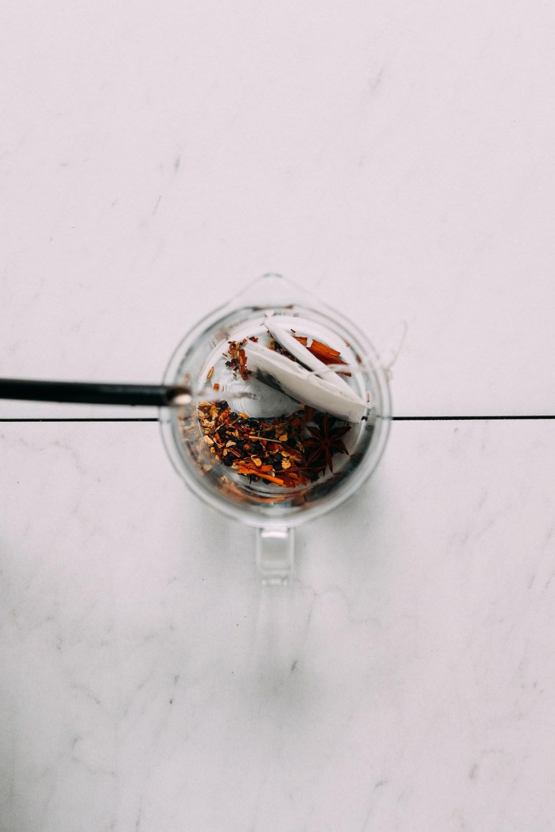 Imagen de arriba del agua caliente que se vierte sobre té negro y especias en un frasco transparente