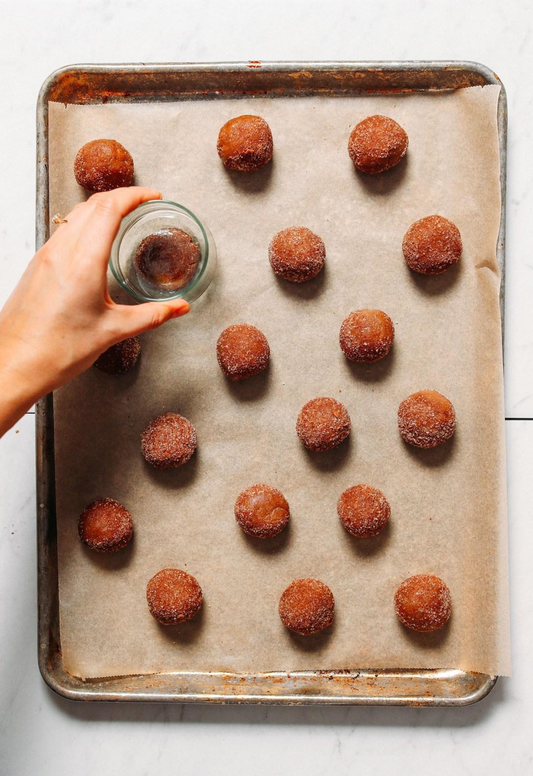 Usar un vaso para aplanar un lote de nuestras galletas veganas sin gluten Snickerdoodle