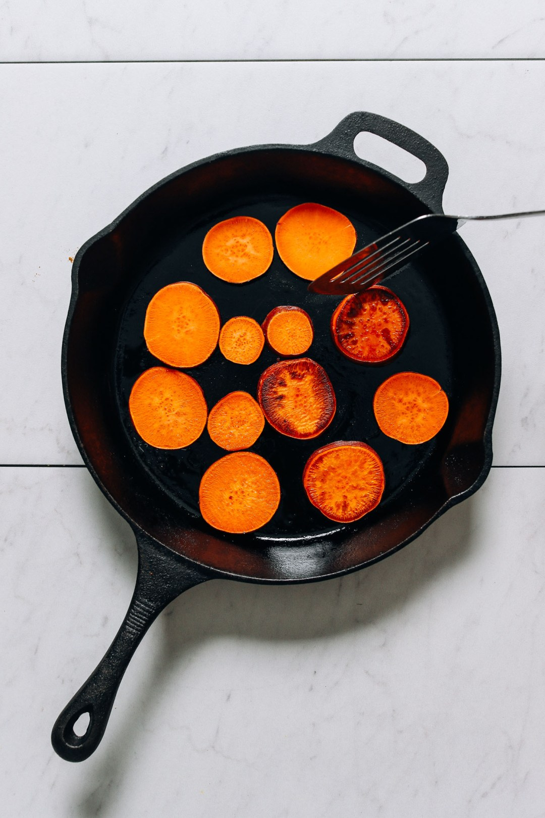 Cocinar rodajas de camote en una sartén de hierro fundido