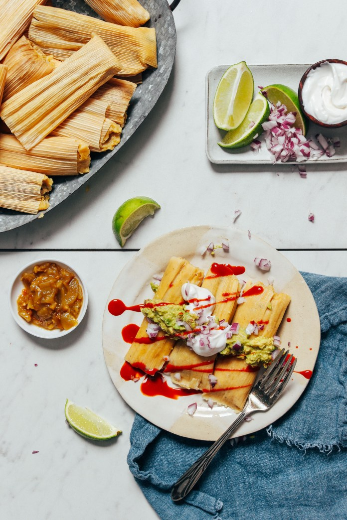 Tray and plate of tamales with toppings