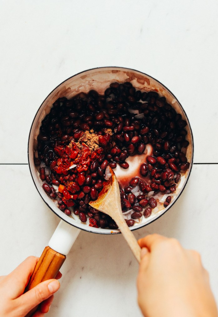 Using a wooden spoon to stir a pot of black beans and spices