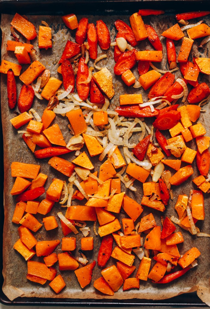 Baking sheet of roasted onion, garlic, carrots, and butternut squash