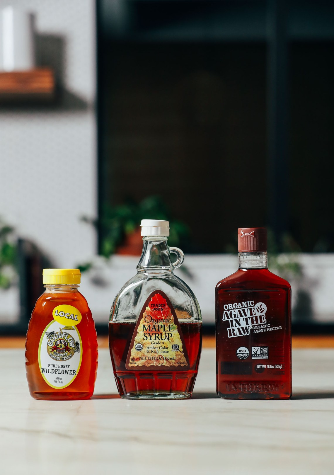 Bottles of honey, maple syrup, and agave