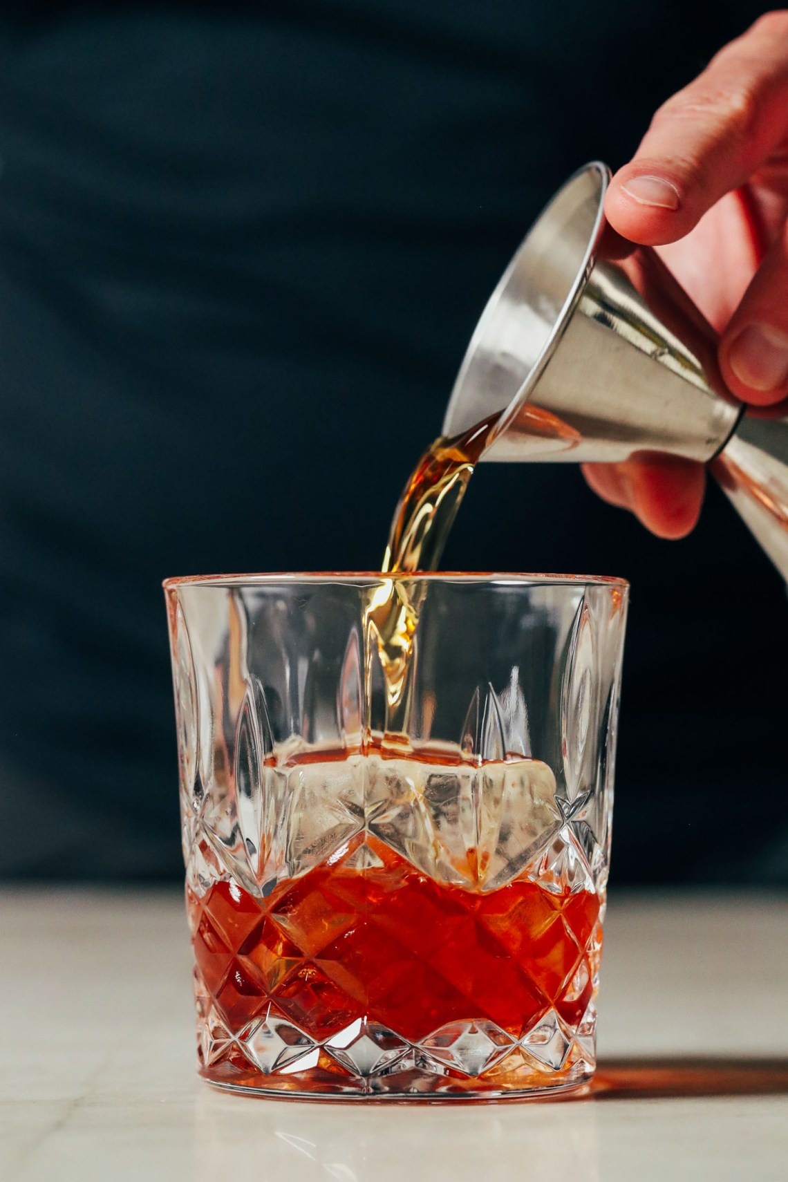 Pouring bourbon over a clear ice cube in a glass