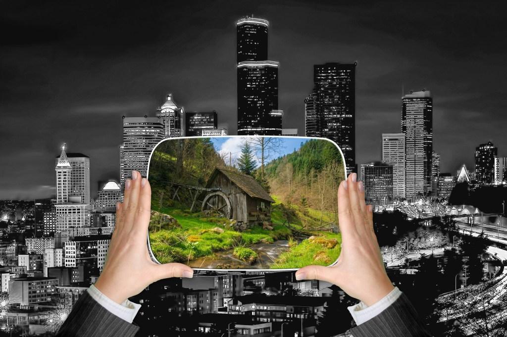 zwei Hände halten das Bild einer Hütte in der Natur vor den grau hinterlegten Hintergrund einer Großstadt