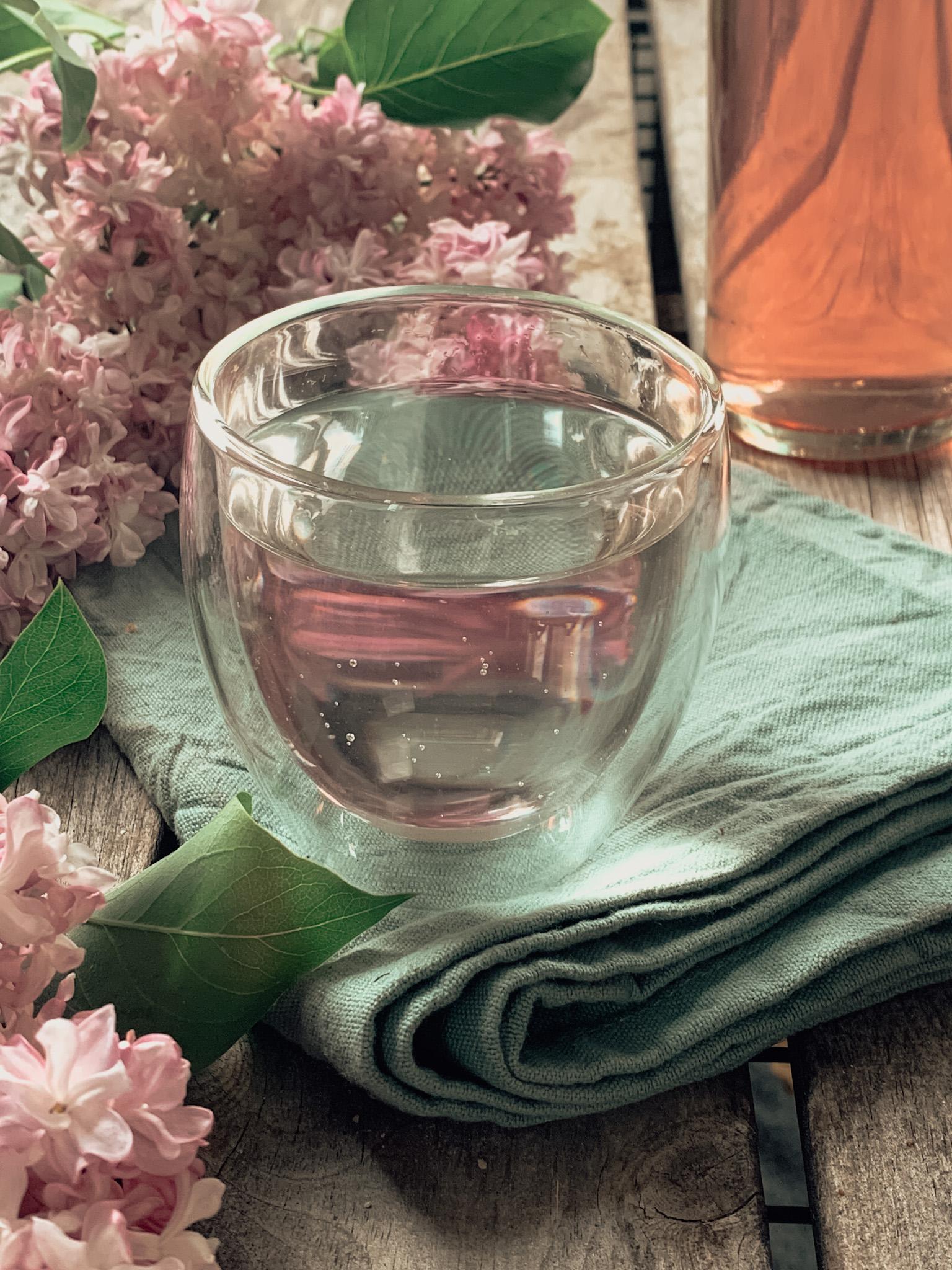 Ein Glas Wasser mit Fliedersirup und Deko aus Fliederblüten