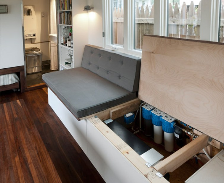 The 8.5′ couch/guest bed opens up to reveal storage, a 40 gal water tank, and water filter. An onboard 3 stage Doulton filter system originally designed for freshwater boaters makes collected rainwater water potable for shower and sinks.